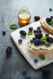 Nya söta Blackberry, blåbärbruschetta, rostat bröd med keso, honung i ett vitt bräde arkivbild