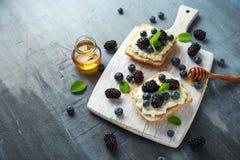 Nya söta Blackberry, blåbärbruschetta, rostat bröd med keso, honung i ett vitt bräde arkivfoton