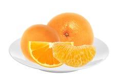Nya saftiga apelsiner på den isolerade vita plattan Royaltyfri Bild