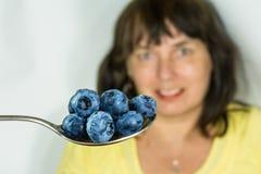 Nya saftiga blåbär på en rostfri tesked Vacciniummyrtillus arkivbilder
