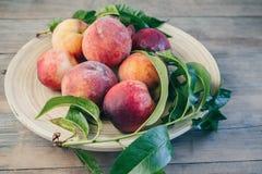 Nya saftiga persikor med sidor på mörk trälantlig bakgrund Arkivbild