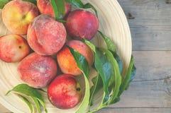 Nya saftiga persikor med sidor på mörk trälantlig bakgrund Arkivfoto
