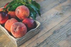 Nya saftiga persikor med sidor på mörk trälantlig bakgrund Royaltyfria Bilder