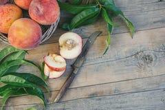 Nya saftiga persikor med sidor på mörk trälantlig bakgrund Royaltyfria Foton