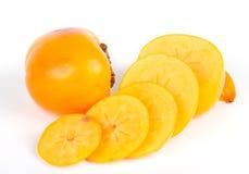 Nya saftiga persimmons med skivor på white Arkivbilder