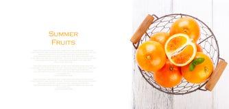 Nya saftiga sommarblodapelsiner i en tappningkorg med mintkaramellbladet på trätabellen på en vit bakgrund med kopieringsutrymme Royaltyfri Foto
