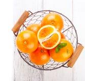 Nya saftiga sommarblodapelsiner i en tappningkorg med mintkaramellbladet på trätabellen på en vit bakgrund med kopieringsutrymme Royaltyfria Bilder