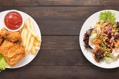 Nya sallad och stekt kyckling- och fransmansmåfiskar på träbacen Arkivfoto