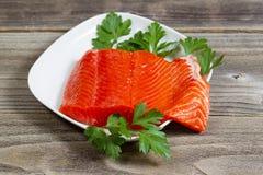 Nya Salmon Fillet i den vita maträtten på lantligt trä Arkivbilder