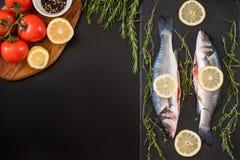nya seabass, rosmarin, tomat, citron, peppar och kryddor på tabellen Arkivfoto