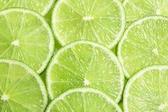 Nya skivade mogna limefrukter som bakgrund Fotografering för Bildbyråer