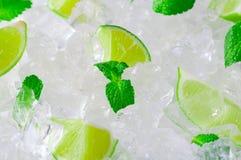 Nya skivor av gröna limefrukter och mintkaramellen över krossade iskuber Fotografering för Bildbyråer