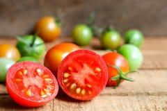 Nya små tomater med den gröna stammen på träbakgrund Royaltyfri Fotografi