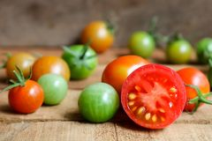 Nya små tomater med den gröna stammen på träbakgrund Royaltyfria Foton