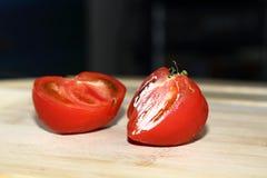 Nya små tomater som klipps upp på en skärbräda i förberedelsen för att laga mat Arkivbilder