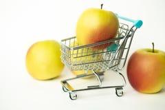 Nya smakliga äpplen i lagervagnar Begrepp för att inhandla i speceriaffären arkivbild
