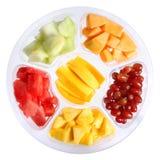Nya stycken av frukter i den plast- behållaren som isoleras på vit Arkivbilder