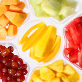Nya stycken av frukter i plast- behållare. Arkivfoto