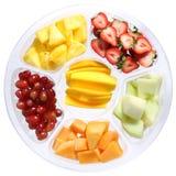 Nya stycken av frukter i plast- rundar behållaren som isoleras på vit. Olika sorter av skivade frukter Royaltyfria Bilder