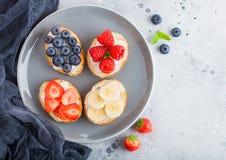 Nya sunda mini- smörgåsar med gräddost, frukter och bär i grå platta med torkduken Jordgubbar blåbär, knäpp a royaltyfri foto
