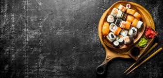 Nya sushirullar i en platta på en skärbräda med pinnar och såser royaltyfri bild