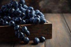 Nya svarta druvor i mörkt trämagasin på trätabellen arkivfoto