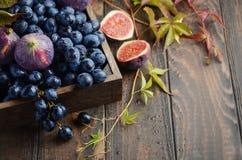 Nya svarta druvor och fikonträd i mörkt trämagasin på trätabellen arkivfoto