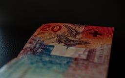 Nya tjugo schweizisk franc genomskinlig isolerad svart bakgrund royaltyfria foton