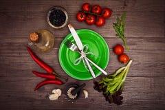 Nya tomater, chilipeppar och andra kryddor och örter runt om den moderna gröna plattan i mitten av trätabellen Top beskådar Dela  Arkivbilder