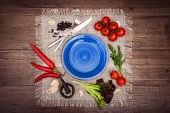 Nya tomater, chilipeppar och andra kryddor och örter runt om modernt mörker - blå platta i mitten av trätabell- och torkdukenapk Arkivfoton