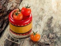 Nya tomater i en bunke på åldrigt trä Arkivfoto
