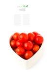 Nya tomater i en hjärtaform som isoleras på vit Fotografering för Bildbyråer