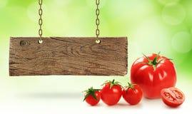 Nya tomater och träbräde royaltyfria bilder