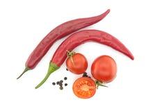 Nya tomater och varma peppar som isoleras på vit bakgrund Till Arkivfoton