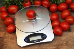 Nya tomater på kökvågvägning Royaltyfri Foto