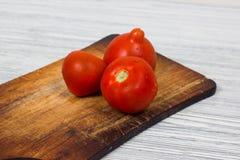 Nya tomater på tappningträskärbräda och träbakgrund Royaltyfri Bild