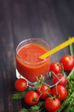 Nya tomatfruktsaft och tomater med gräsplaner Arkivfoto