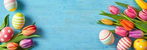Nya tulpan och påskägg i ett färgrikt baner arkivfoton