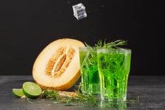 Nya två och kalla coctailar för sommar med iskuber, dragonsidor och nära en halva av en melon på en svart bakgrund Förnyande D Arkivbild