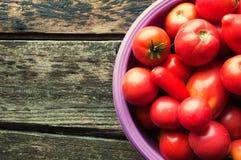 Nya unga tomater i en bunke på en träbakgrund Arkivbild