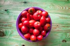 Nya unga tomater i en bunke på en trägräsplan gör sammandrag backgr Arkivfoto