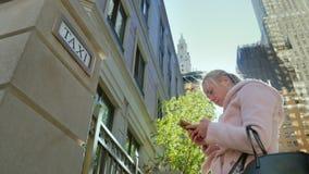 nya USA york En ung kvinna använder en smartphone på bakgrunden av skyskrapor, och tecknet med en taxi undertecknar stock video