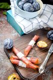 Nya valda plommoner i krukmakeribunke och plommonpastill på mörker b royaltyfria foton