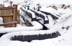 Nya vattenrör som monterar i en jordning i vinter Arkivfoto