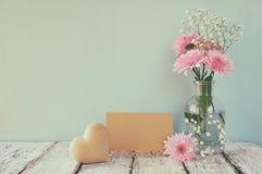 Nya vit- och rosa färgblommor, hjärta bredvid tomt kort för tappning över trätabellen Royaltyfria Bilder