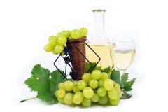 Nya vita druvor med gröna sidor, koppen för vinexponeringsglas och vinflaskan som fylls med vitt vin som isoleras på vit Arkivbild