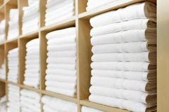 Nya vita hotellhanddukar vikta och som staplas på en hylla fotografering för bildbyråer