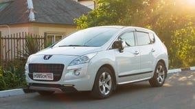 Nya vita Peugeot 2008 som parkeras på den förorts- vägen Arkivfoton