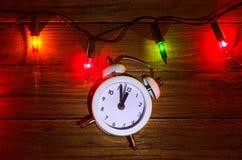 Nya Year& x27; s-ljus och klocka på en trätabell, bästa sikt Arkivbild