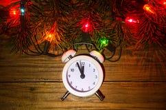 Nya Year& x27; s-ljus och klocka på en trätabell, bästa sikt Royaltyfri Fotografi